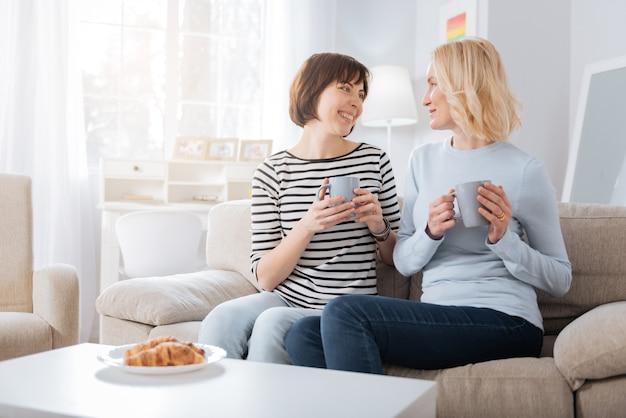 차 시간. 집에서 시간을 즐기면서 서로를 바라보고 차를 마시 며 즐거운 기뻐 젊은 여성들