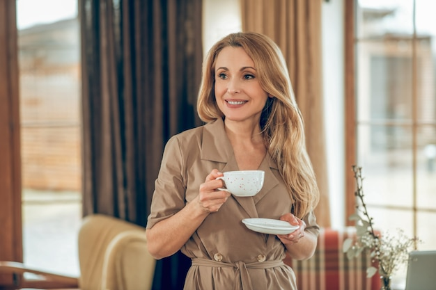 Tea time. long-haired elegant woman having tea and looking contented