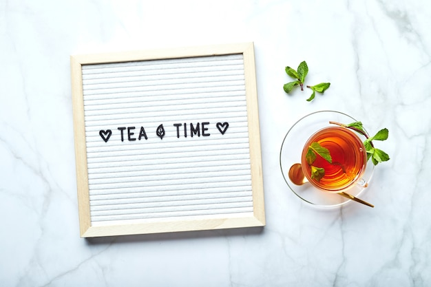 Tea time white letter board with text on marble table with glass cup of tea with mint leaves