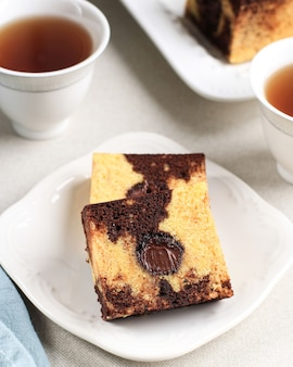 대리석 여행 케이크 조각이 있는 티타임, 중앙에 녹인 초콜릿이 있는 스퀘어 케이크. 하얀 접시에 제공