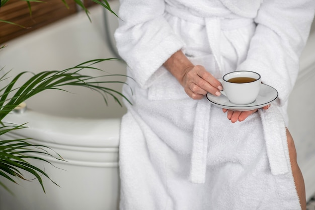 Tea time. woman in a white robe holding a cup with tea