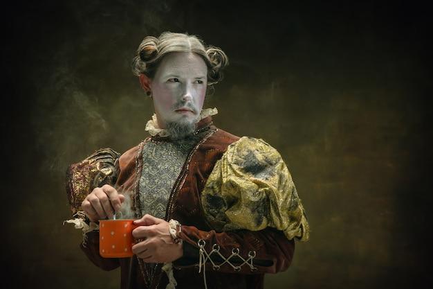 Время чая. молодой человек в роли иоганна баха, изолированного на темно-зеленом фоне. ретро стиль, сравнение концепций эпох. красивая модель-мужчина, как исторический персонаж, великий композитор, старомодный.