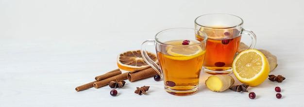 Чай для повышения иммунитета. согревающий лечебный чай с лимоном, имбирем, корицей и клюквой. баннер на белом фоне. фото высокого качества