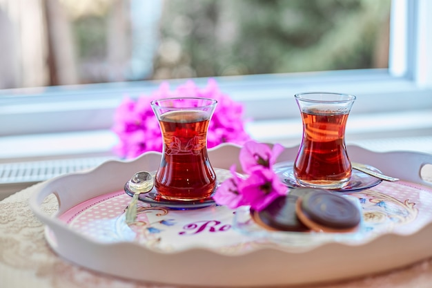 Tea in traditional turkish glass tea glasses on the table with cookies