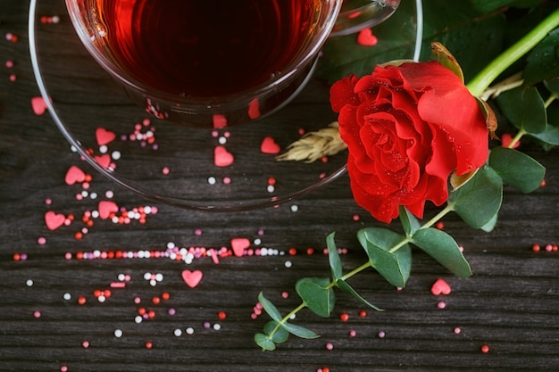 Tea in a transparent cup, color candies and a red rose on dark