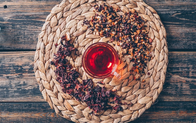 Tè in un sottopentola con vista dall'alto di erbe di tè su un fondo di legno scuro