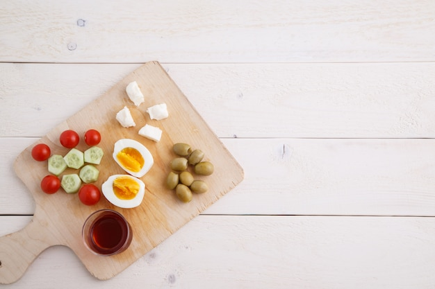 Tea and turkish, mediterranean breakfast on a light wooden tray on a white natural table