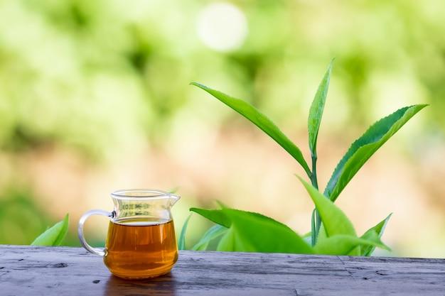木製のテーブルと茶葉のプランテーションのガラスの瓶にお茶の水がボケ味の背景をぼかす