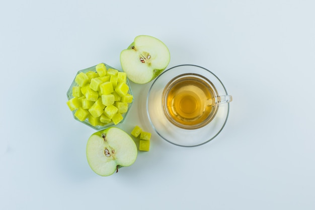 Tea with apple, sugar cubes in a mug on white background, flat lay.