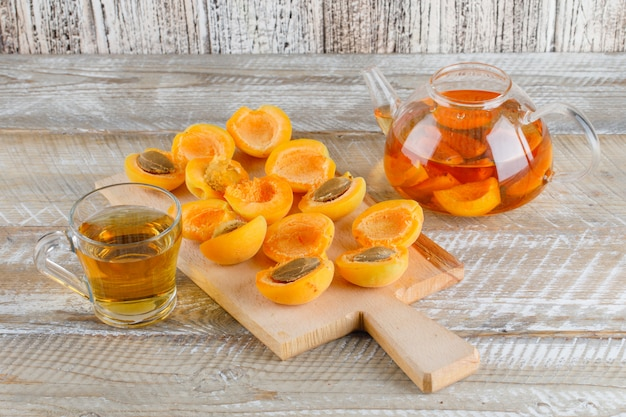 Tea with apricots in teapot and mug on wooden and cutting board, top view.