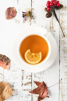 Tea with autumn leaves on shabby surface