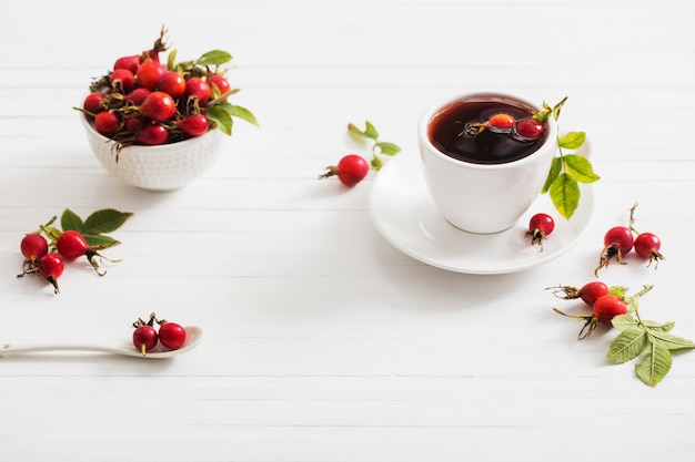Tea with berries of a dogrose on a wooden table