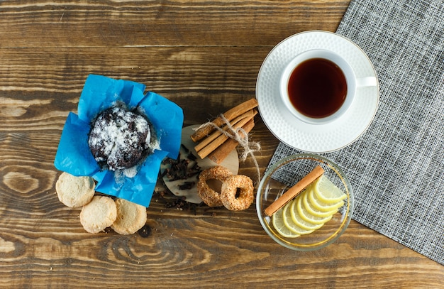Tea with biscuits, cloves, lemon slices, cinnamon sticks in a cup on wooden surface