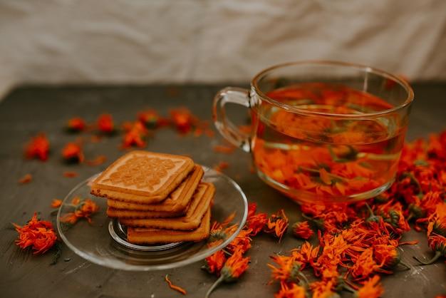 금송화 꽃과 비스킷을 곁들인 차. 투명한 유리 컵과 접시.