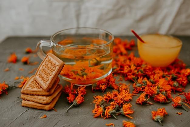Чай с цветками календулы и печеньем. прозрачное стекло