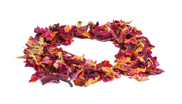 Tea with candied fruit and rose petals on white