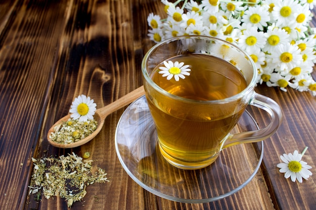 Tea with chamomile in the glass cup on the table