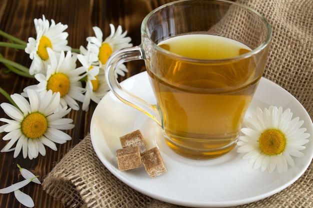 Tea with chamomile in the glass on the old wooden table