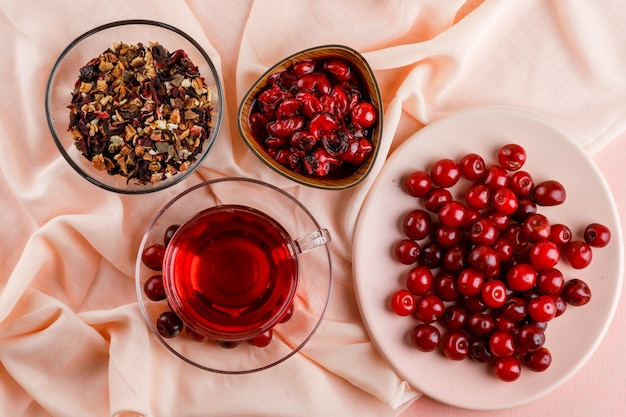 Tea with cherries, jam, dried herbs in a glass mug on pink and textile.