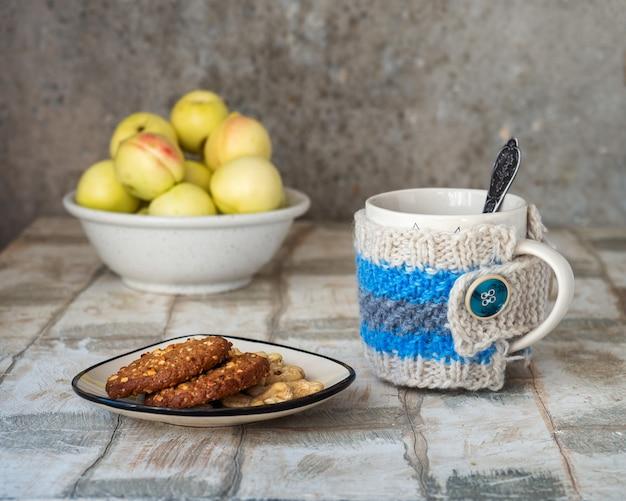 Чай с печеньем овсяное печенье мармелад и орехи на маленькой тарелке кружка с чаем в вазянном фу