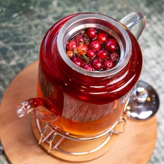 ガラスのティーポットにクランベリーとスパイスを入れたお茶。ビタミンや抗酸化物質が豊富な健康的な食事。ライフスタイル。