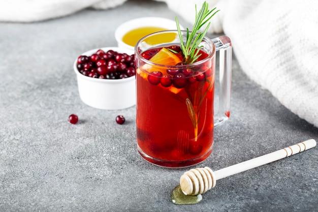 Чай с клюквой, корицей, апельсином, розмарином и медом в стеклянной чашке