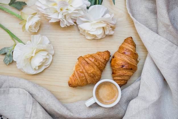 Tea with croissants near beautiful flowers