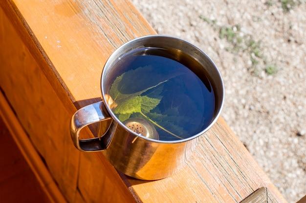 Чай с листьями смородины заваривается в металлической кружке.