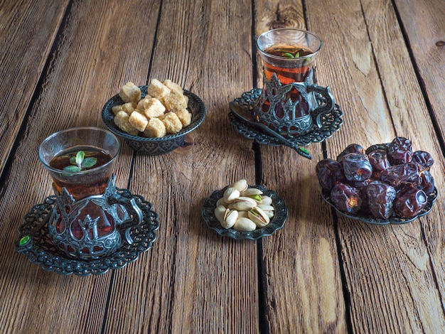 Tea with dates on a dark wooden table.