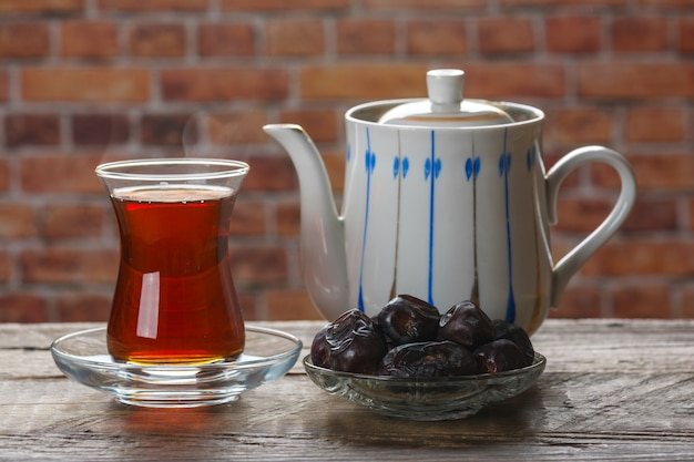 Tea with dates on wooden table