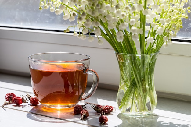 Tea with a dogrose and a bouquet of spring lilies