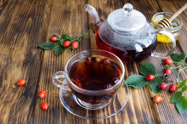 Чай с шиповником в стеклянной чашке и чайник на деревянном столе