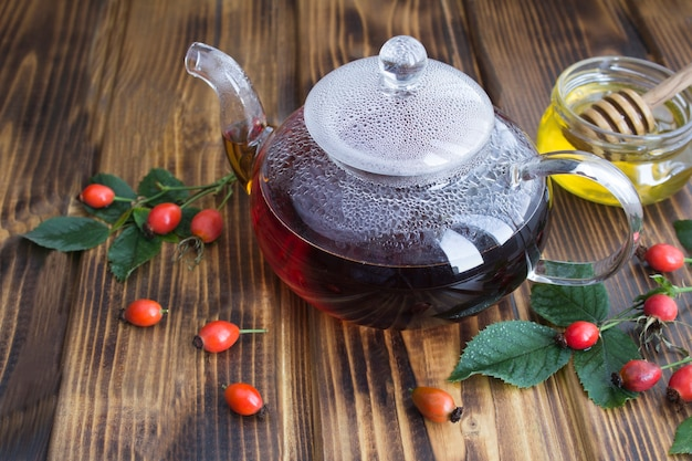 Чай с шиповником в стеклянном чайнике на деревянном столе