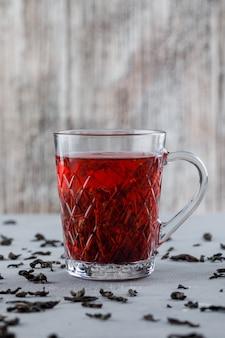 Чай с сухим черным чаем в стеклянной чашке на гипсе и шероховатой поверхности