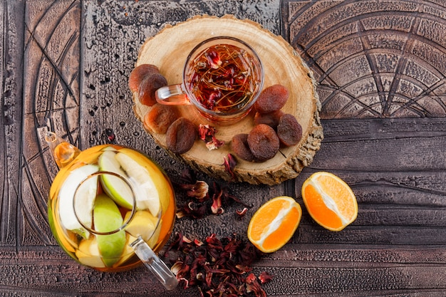 Tea with dried fruits, herbs, fruit infused water, orange, wood in a cup on stone tile surface, top view