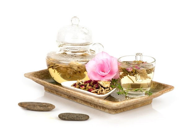 Tea with dried japanese honeysuckle,rose and chrysanthemum flowers isolated on white surface.