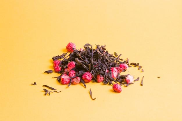 黄色の背景に乾燥イチゴとお茶