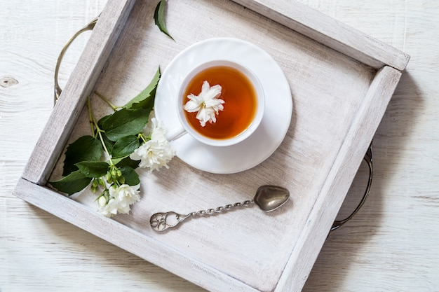 Tea with flower on wooden table