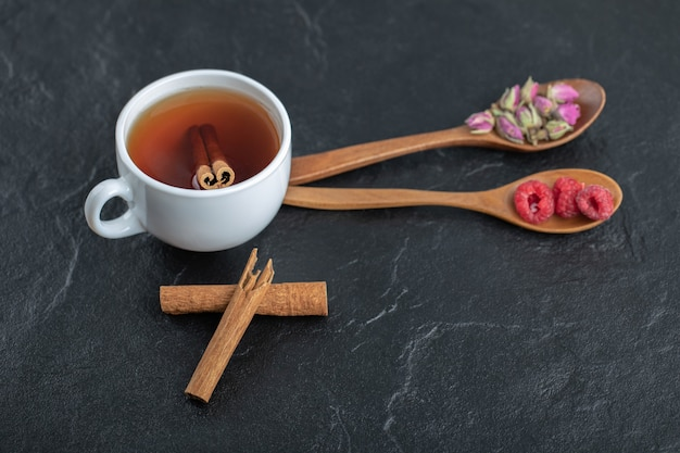 Чай с цветами и малиной на черном столе.