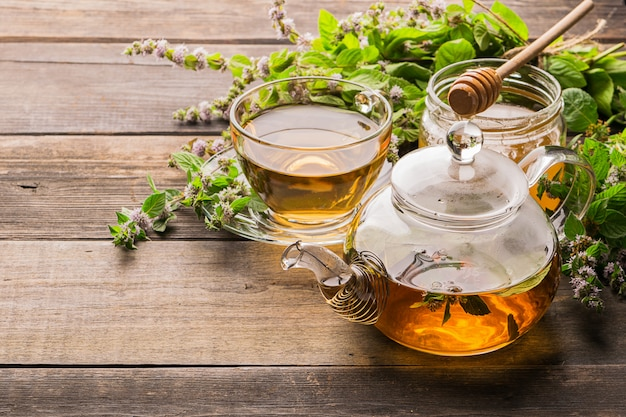 Tea with fresh leaves of lemon balm mint in a cup and teapot on wood