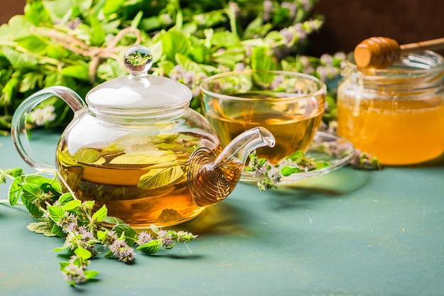 Tea with fresh leaves of lemon balm mint cup and teapot on wood