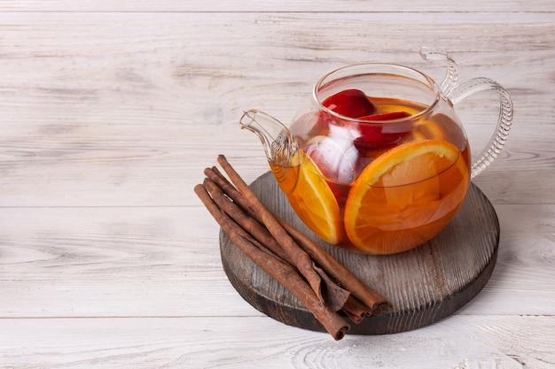 Чай с фруктами и ягодами в стеклянном чайнике на белом деревянном фоне копией пространства