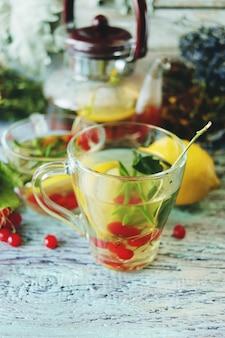 木製の背景にガラスのカップに健康的なハーブの花ベリーとレモンとお茶