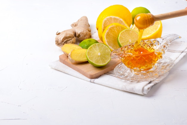 Tea with herbs, lemon and ginger on white background and honey