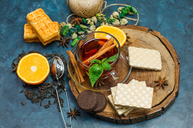 Tea with herbs, orange, spices, biscuits, strainer in a mug on wooden board and stucco background, flat lay.