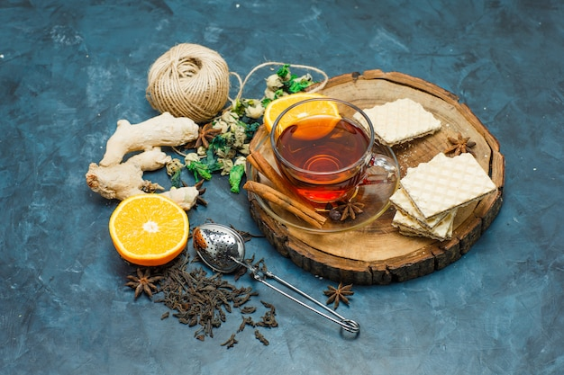 Tea with herbs, orange, spices, waffle, thread, strainer in a mug on wooden board and stucco background, flat lay.