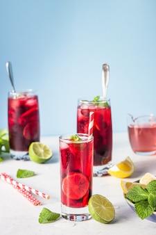 ハイビスカス、ベリー、ミント、柑橘類、氷と影のある太陽の下でお茶。