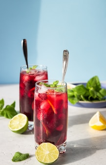 Tea with hibiscus, berries, mint, citrus and ice in the sun with shadows.