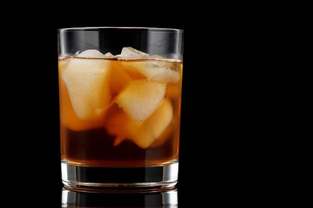 黒の背景にグラスに氷とお茶。