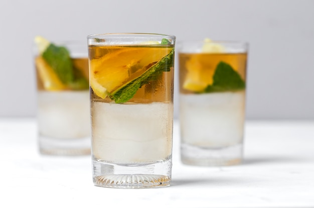 Tea with ice, mint and lemon wedges on white table